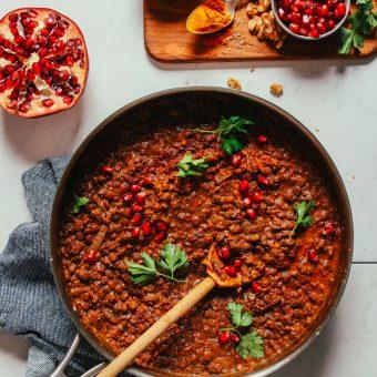 Large skillet filled with a batch of our hearty vegan Lentil Fesenjan recipe