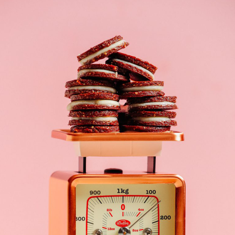 Raw Oreo Cookies piled in two stacks on a vintage scale