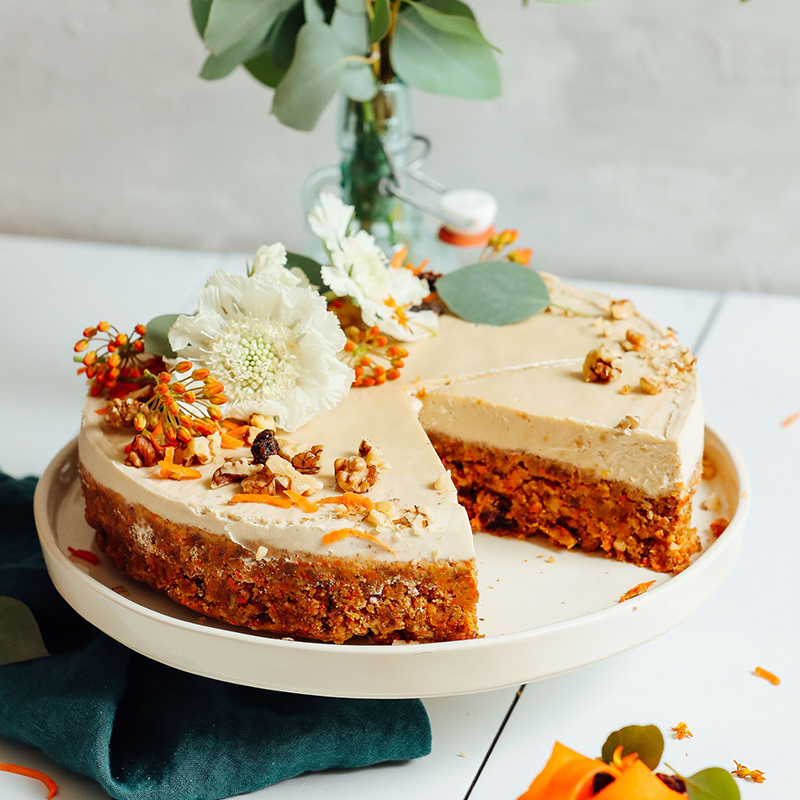 Partially sliced Raw Vegan Carrot Cake decorated with walnuts and fresh flowers