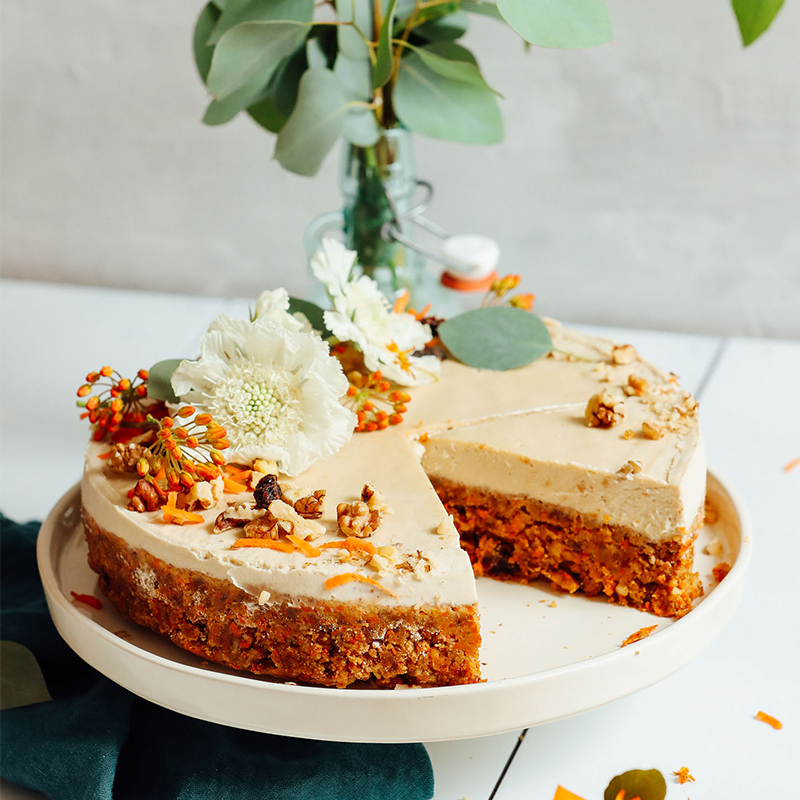 Partially sliced Raw Vegan Carrot Cake topped with flowers, shredded carrot, and walnuts