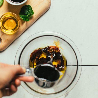 Pouring balsamic vinegar into a bowl for homemade Balsamic Vinaigrette Dressing