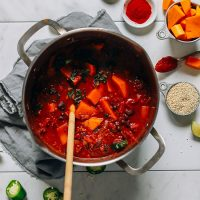 Wooden spoon in a pot of Butternut Squash Chili alongside ingredients used to make it