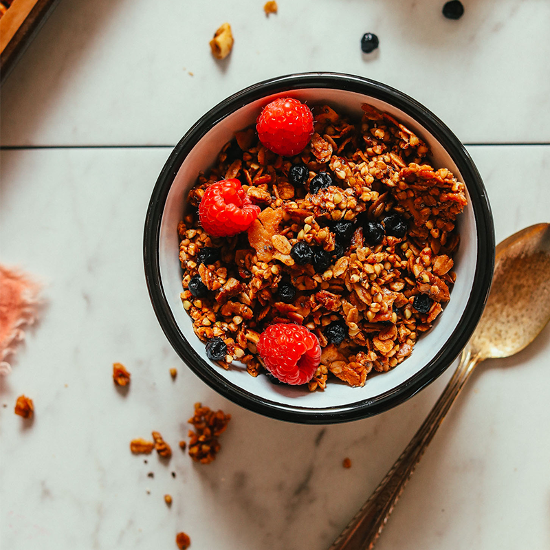 Bowl of Easy Homemade Buckwheat Granola with dried blueberries and fresh raspberries