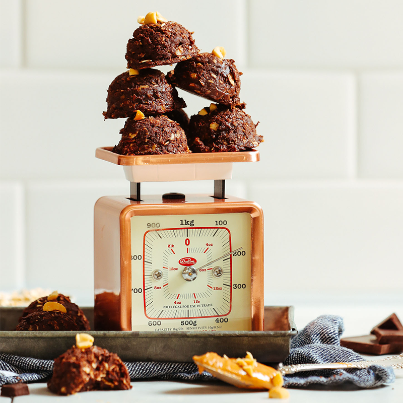 Five Vegan Peanut Butter No-Bake Cookies stacked on a vintage scale