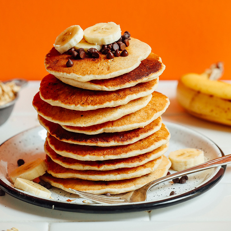 Plate with a tall stack of Banana Oat Pancakes topped with chocolate chips and sliced bananas