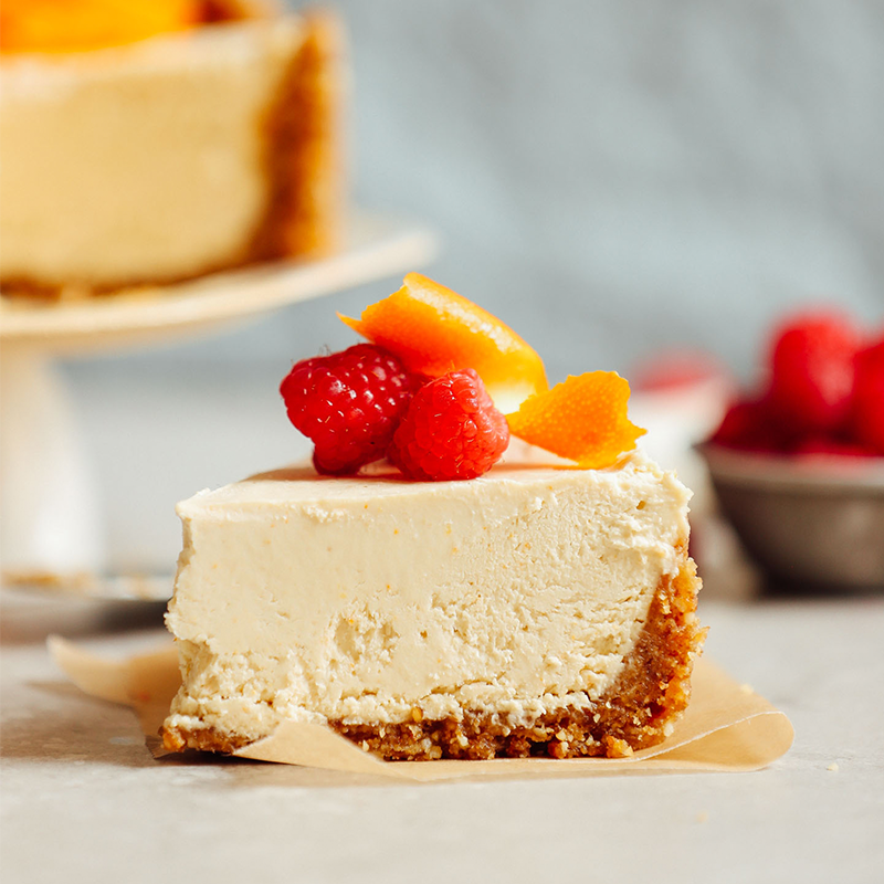 Slice of Vegan Coconut Yogurt Cheesecake with orange peel and raspberries on top
