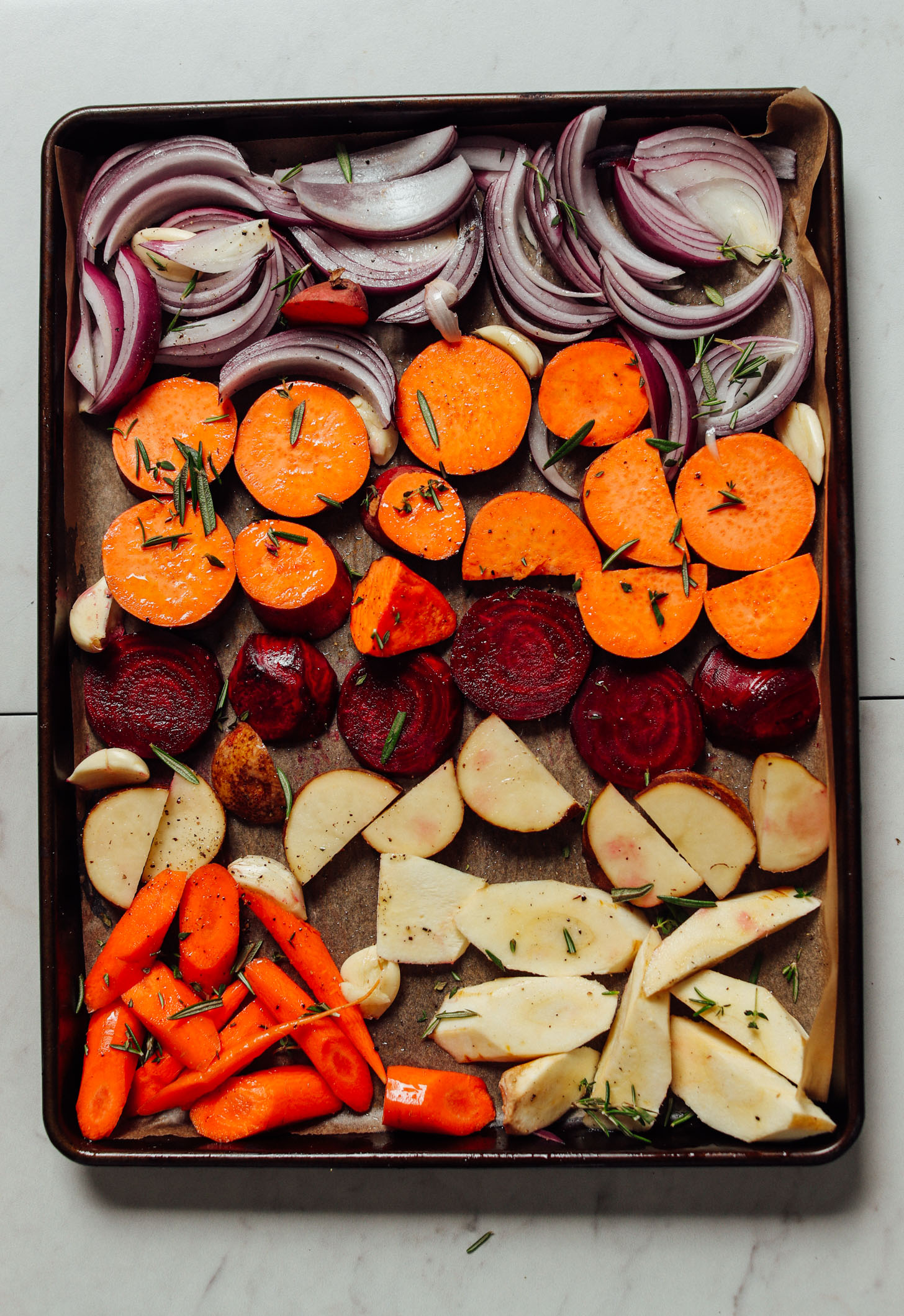 Parchment-lined baking sheet filled with sliced vegetables and herbs for roasting