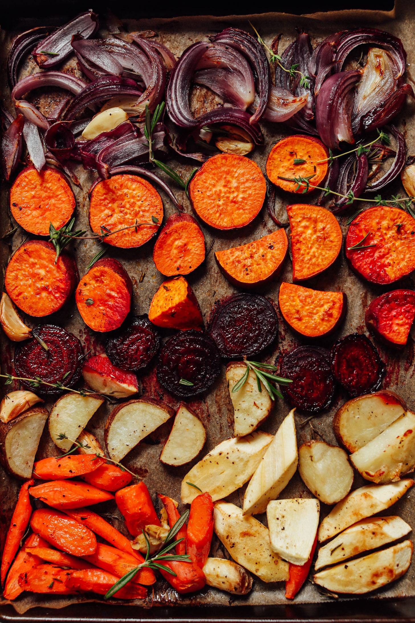 Baking sheet filled with freshly roasted vegetables and herbs for a simple vegan side dish