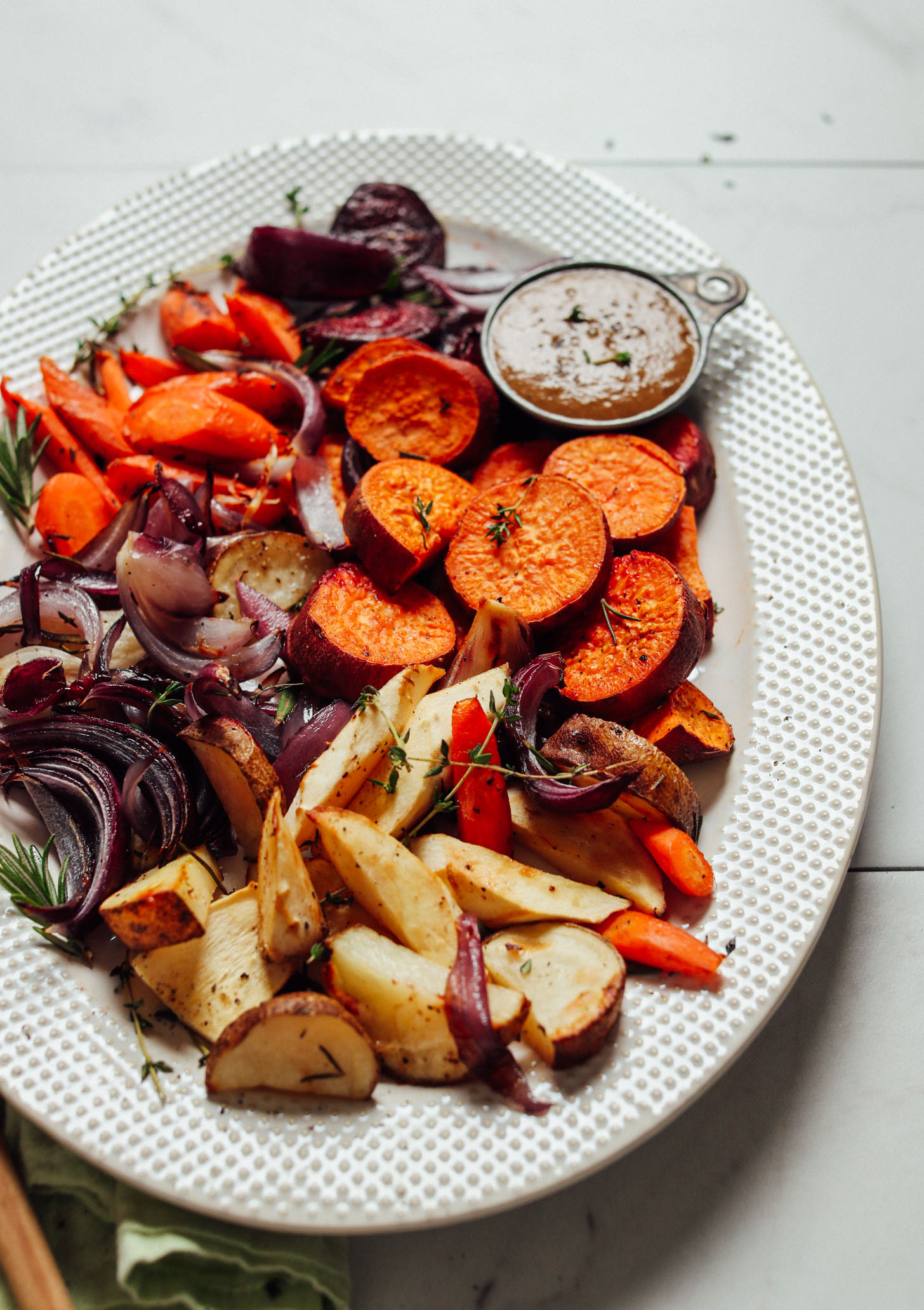 A backlit view of a platter of pan roasted vegetables with vegan gravy