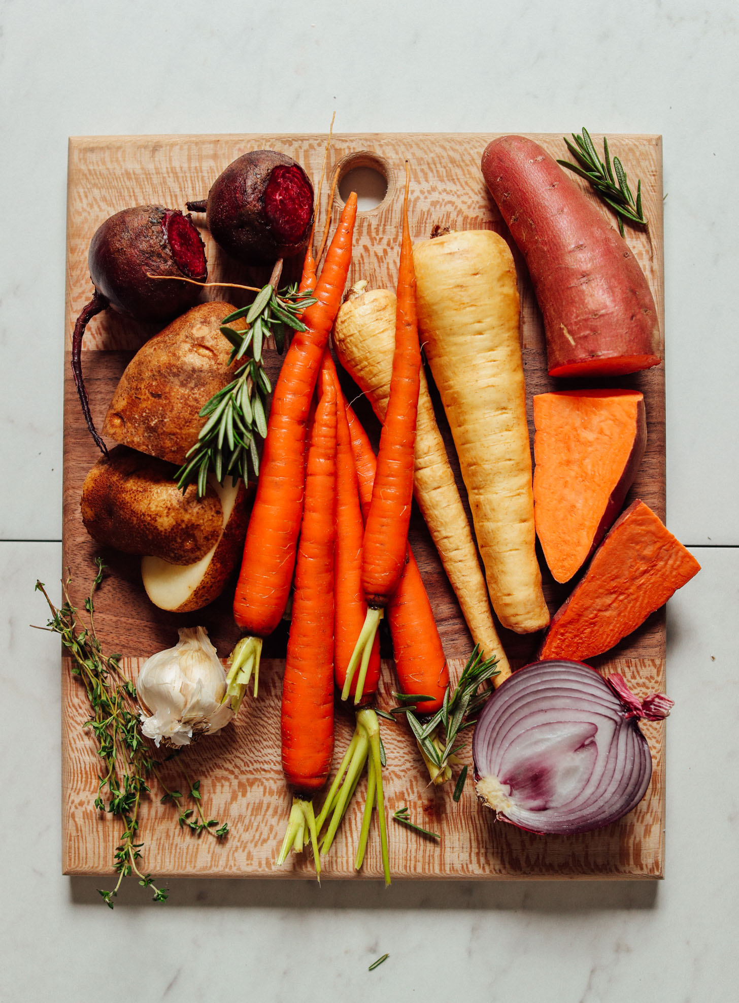 Wood cutting board filled with fresh beets, potatoes, parsnips, carrots, onions, garlic, and herbs for roasting