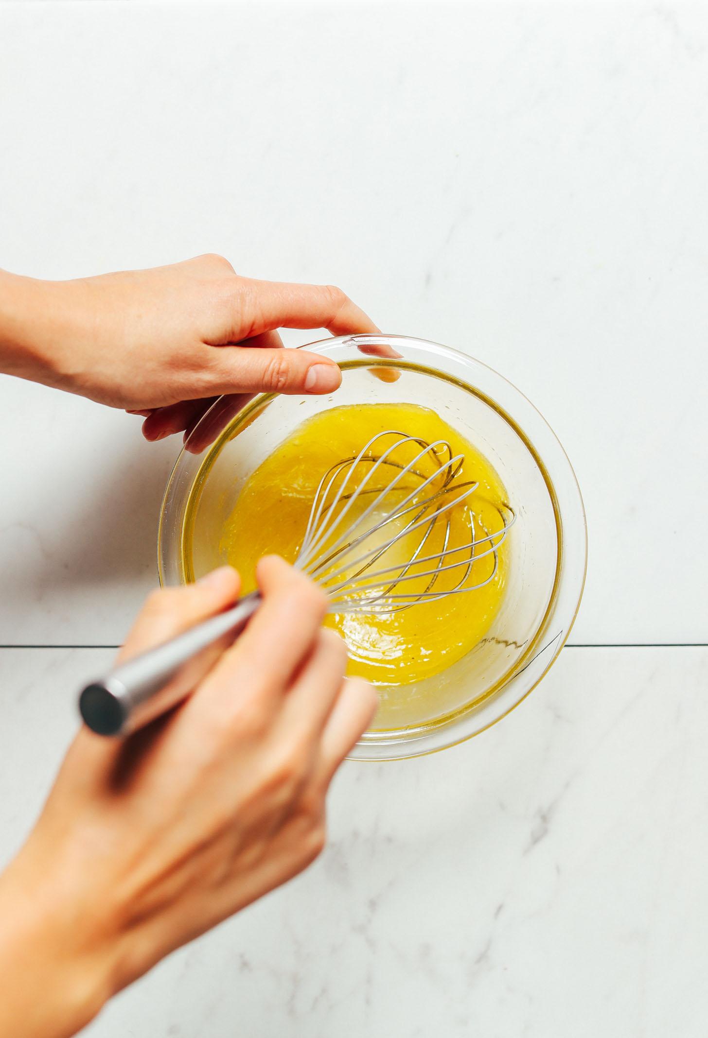 Using a whisk to stir together ingredients for homemade Lemon Vinaigrette