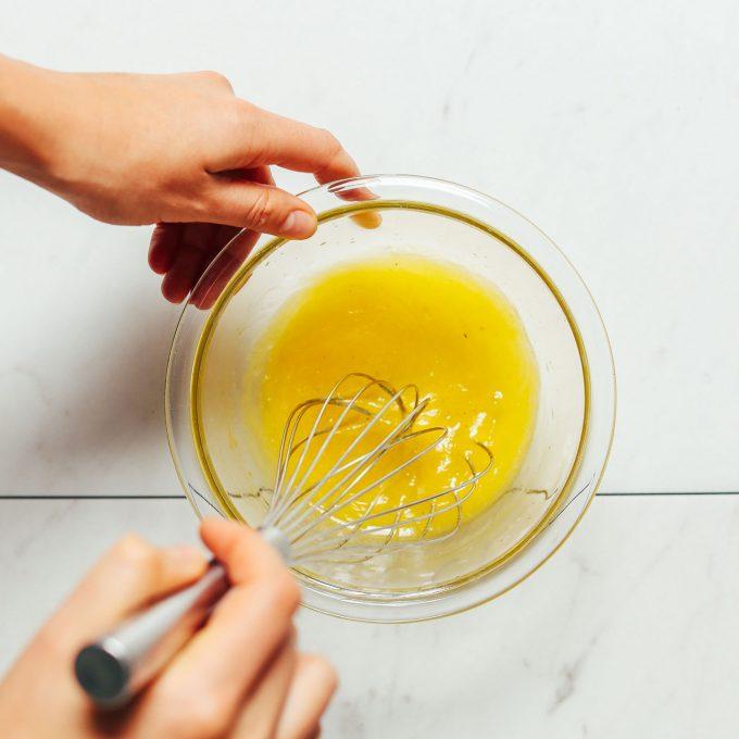 Whisking dressing ingredients in a small bowl to make homemade Lemon Vinaigrette