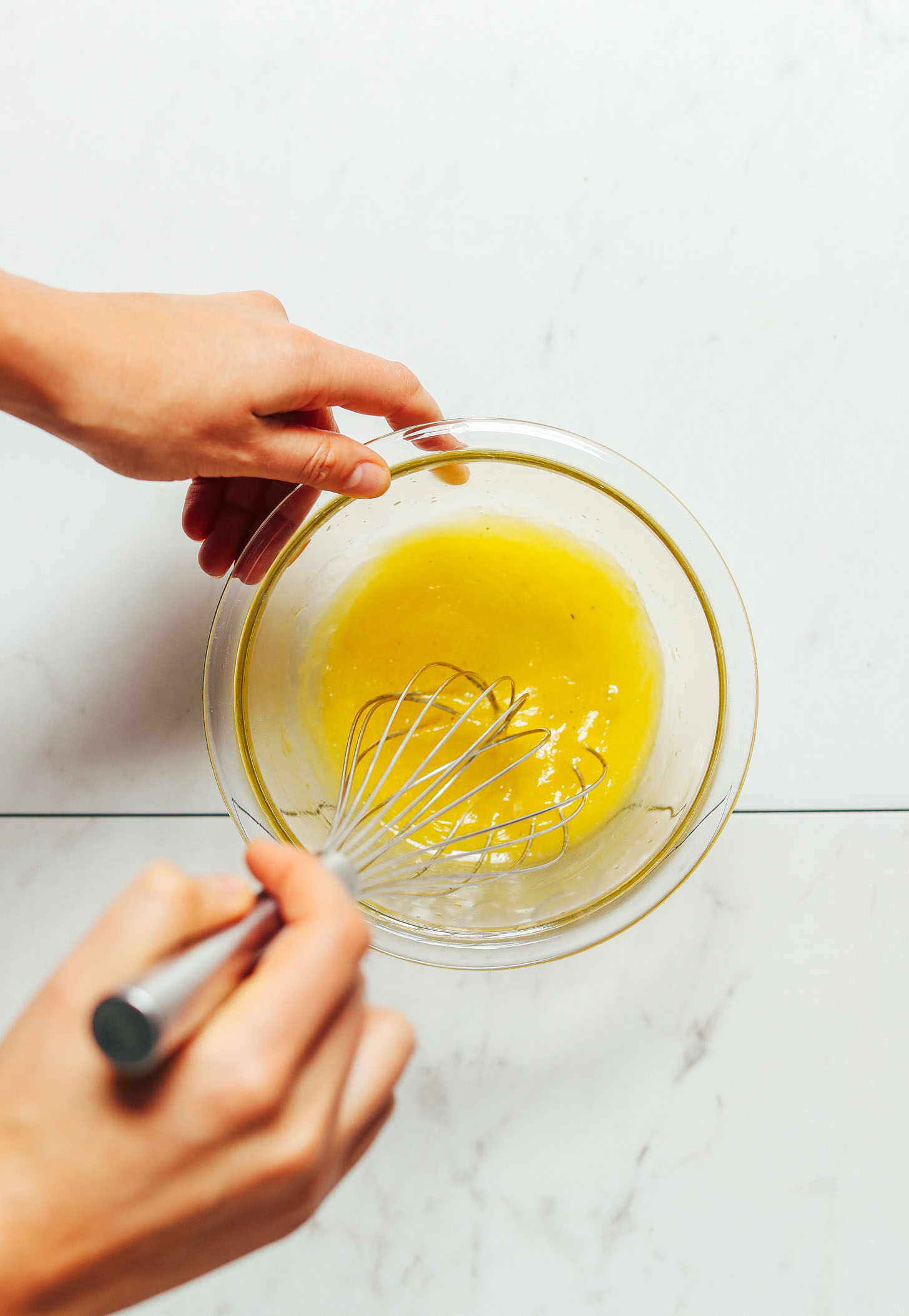 Overhead image of lemon vinaigrette in a glass bowl being whisked by hand