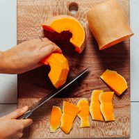 Using a knife to cut the peel off of butternut squash