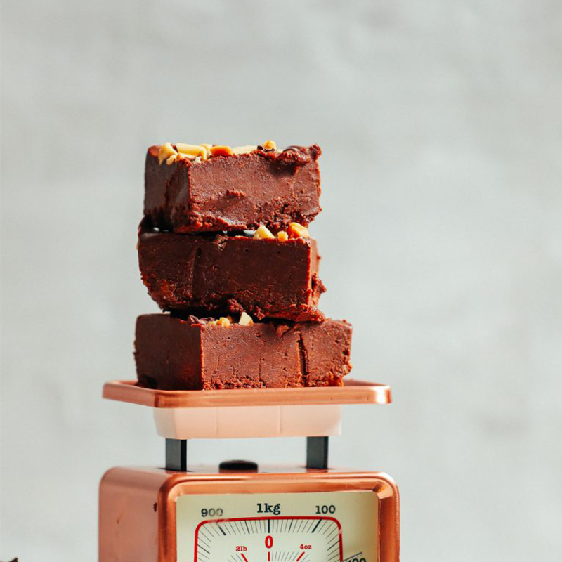 Slices of vegan chocolate peanut butter fudge stacked on a vintage scale