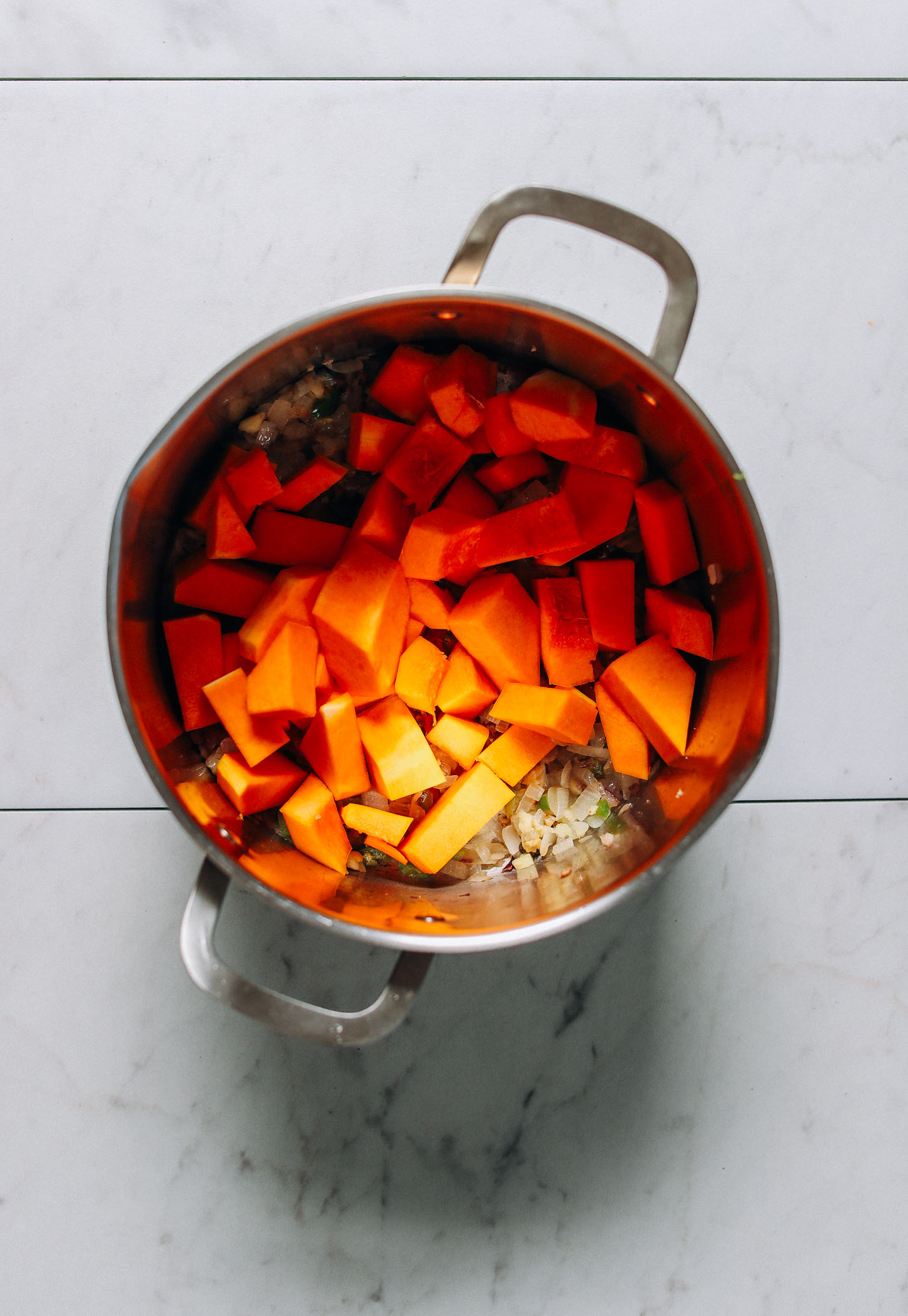 Butternut squash cubes added to a big pot of hearty vegan chili perfect for winter