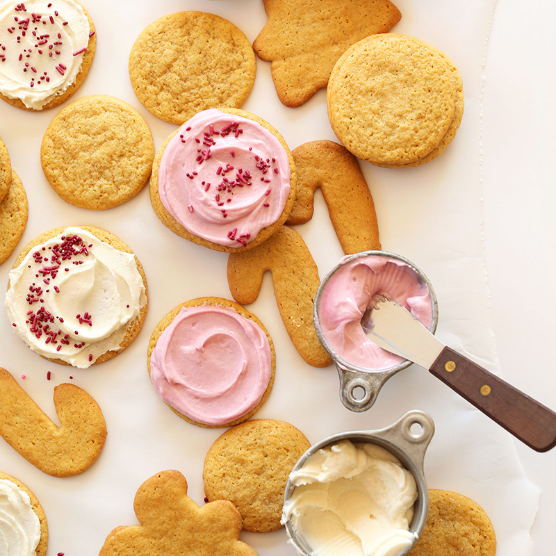 Measuring cups of natural homemade pink and white frosting and various shapes of Vegan Sugar Cookies