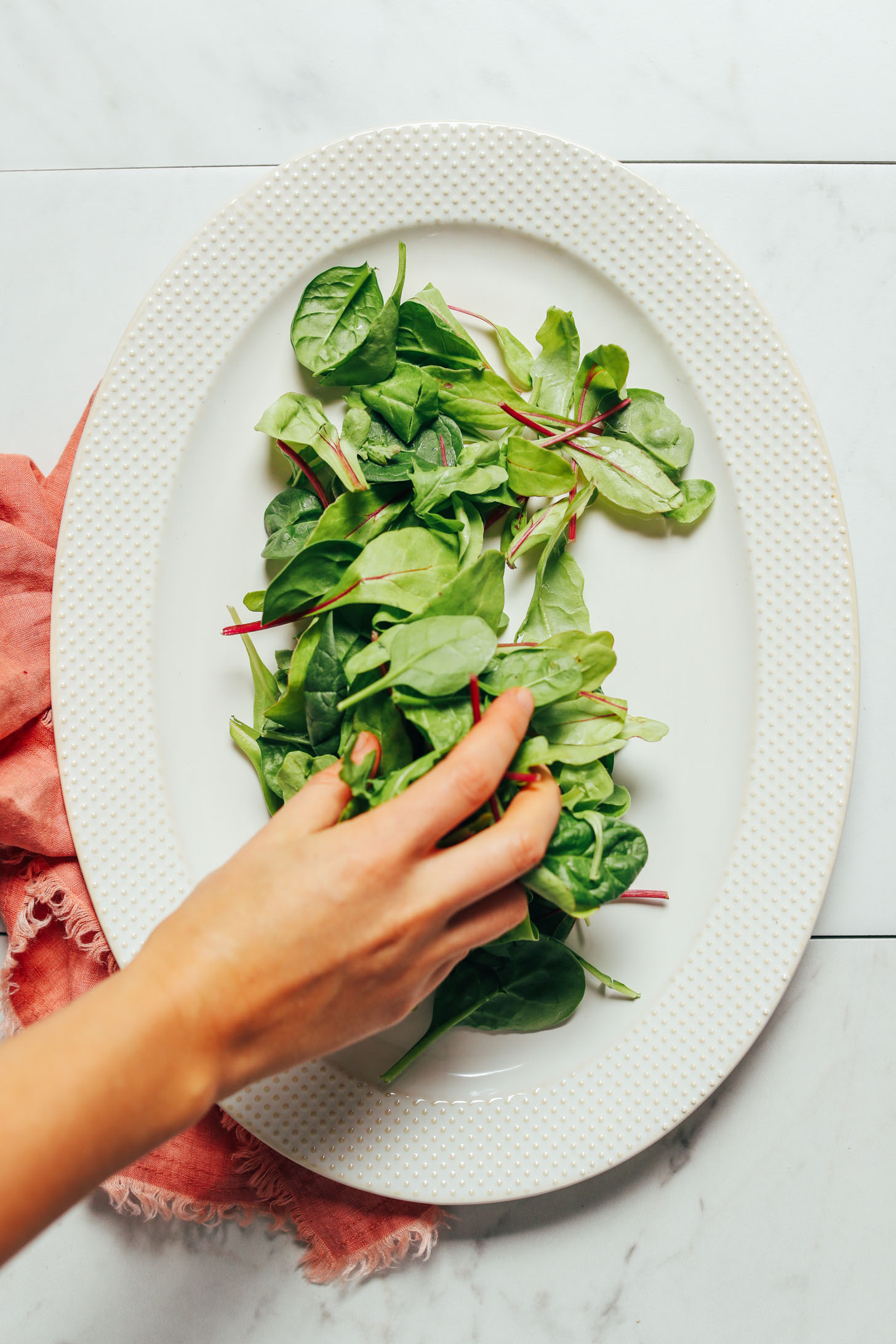 Overhead image of a white platter pink towel and greens being placed on the plate by hand
