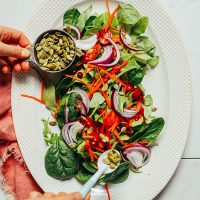 Sprinkling pepitas for our Simple Green Salad recipe