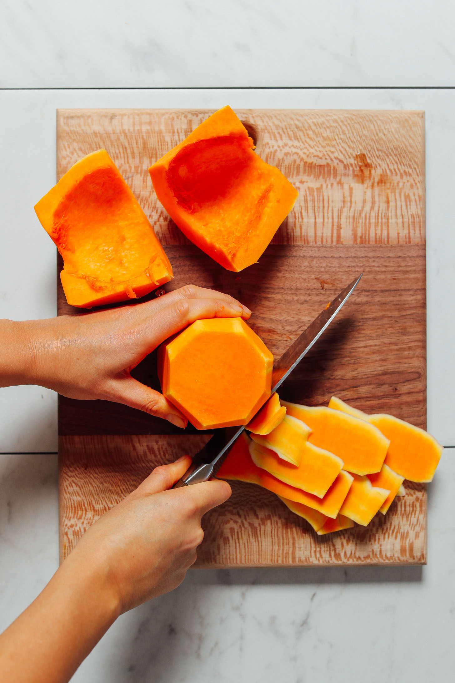 Using a large knife to cut the skin off of a butternut squash