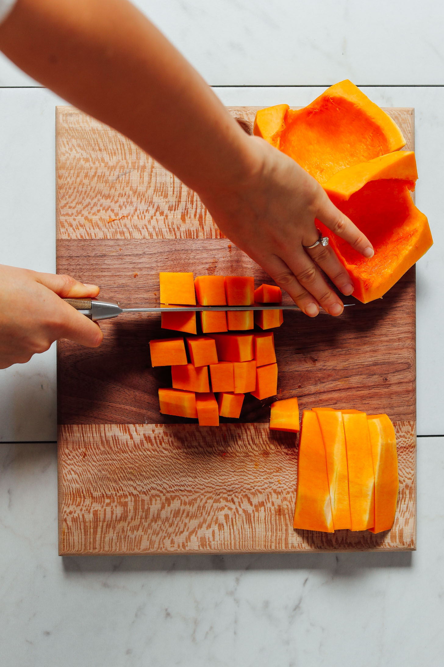 Cutting strips of butternut squash into cubes on a wood cutting board