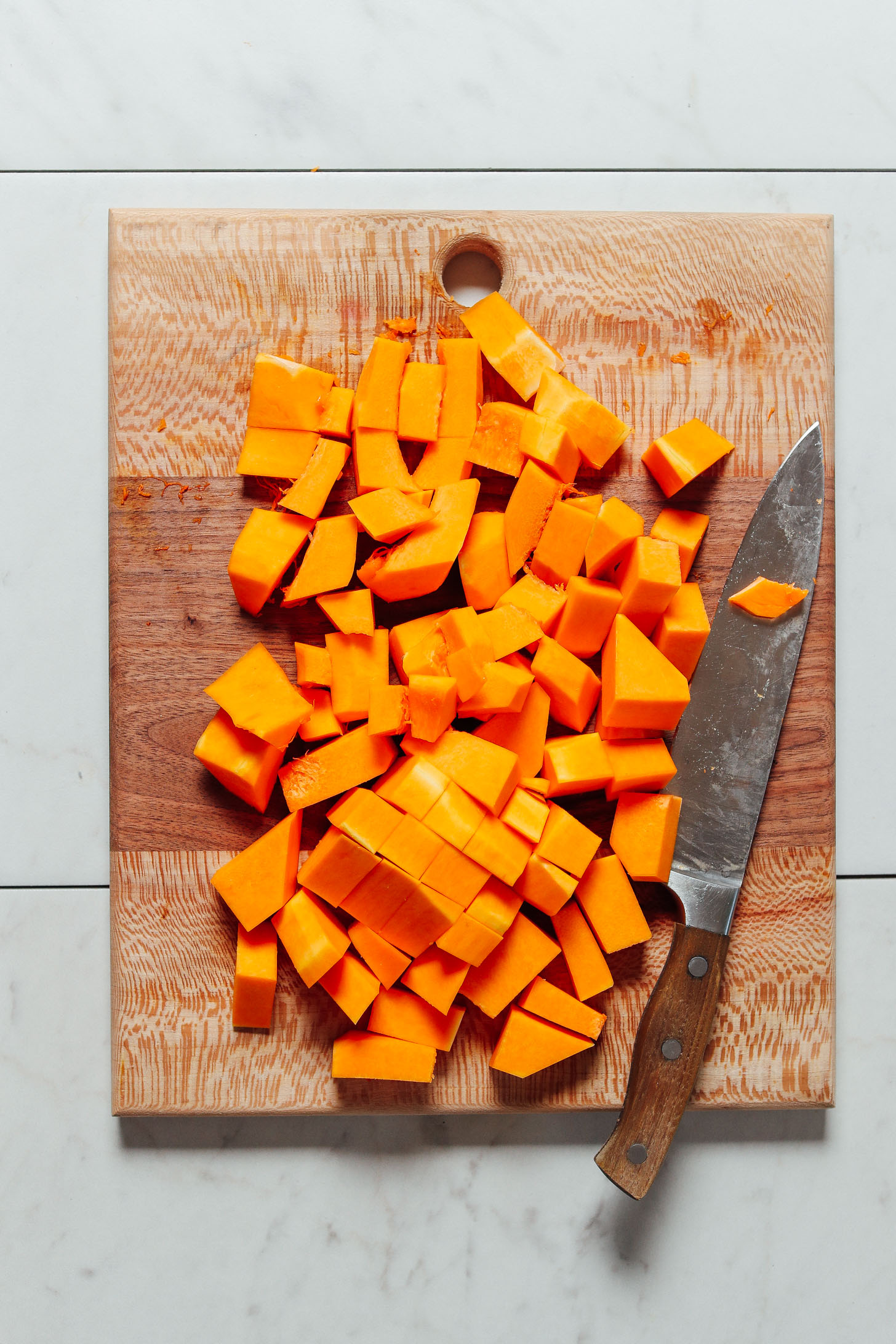 Cutting board filled with cubed butternut squash for our How to Cut Butternut Squash Tutorial