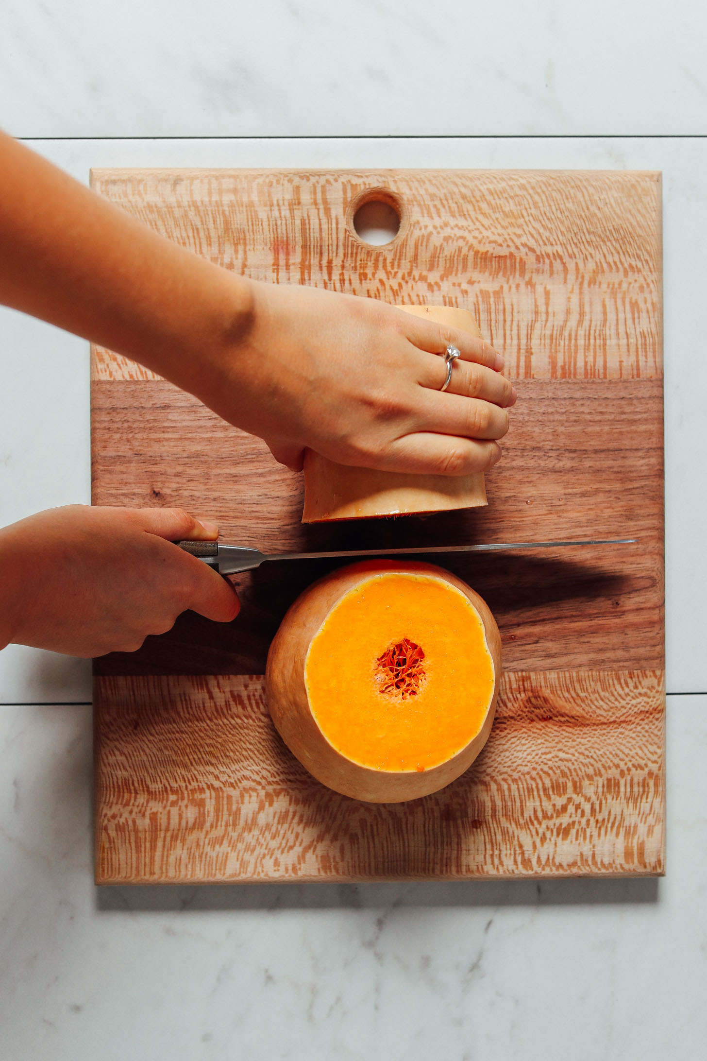 Butternut squash cut in half with the knife held between the two halves