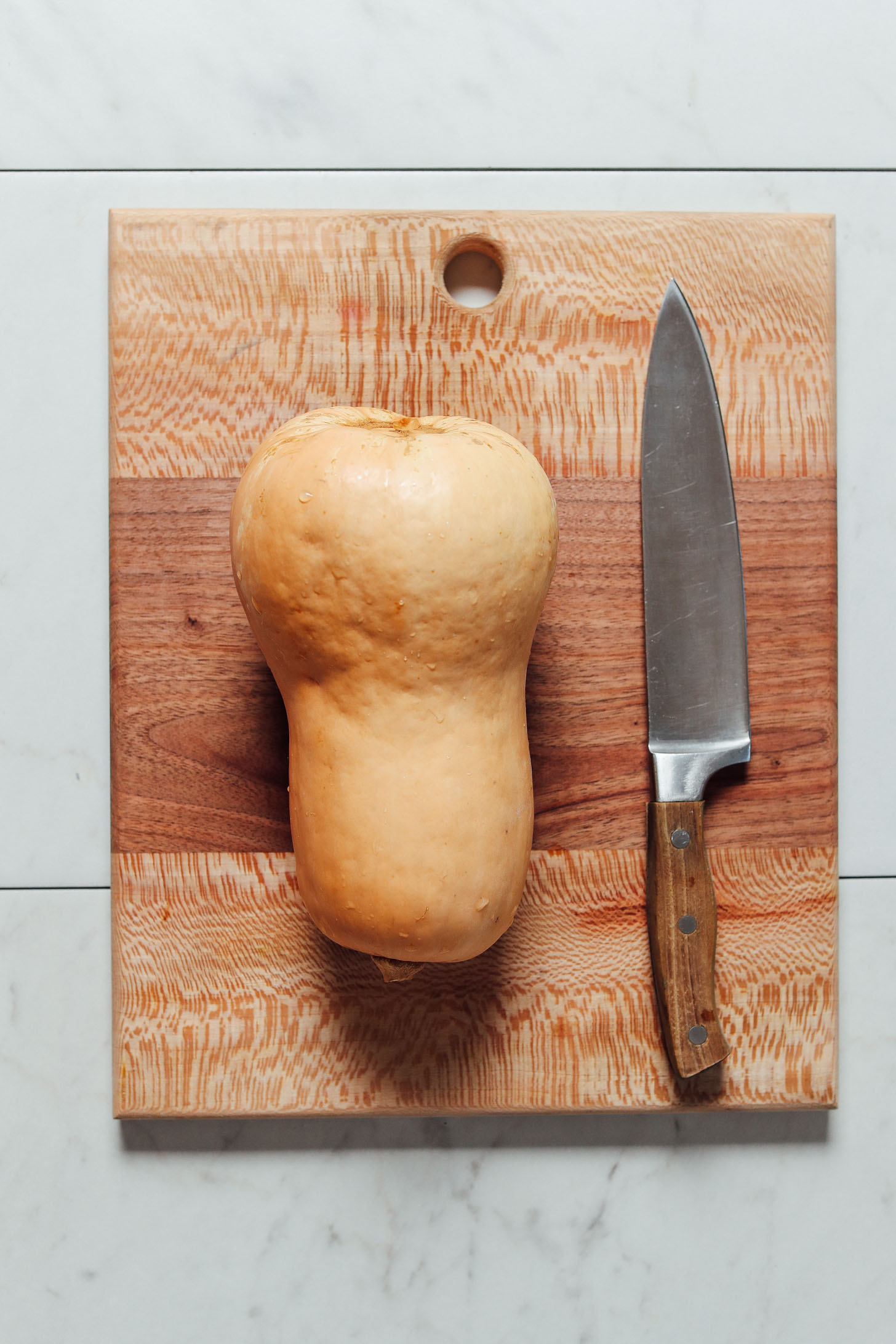 Photo of a knife and butternut squash on a cutting board for our How To Cut Butternut Squash Tutorial