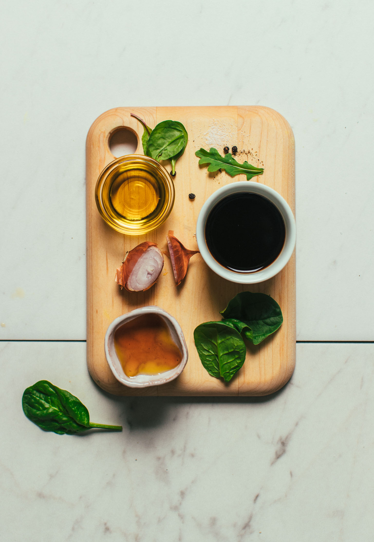 Wood cutting board filled with ingredients for making our balsamic vinaigrette recipe