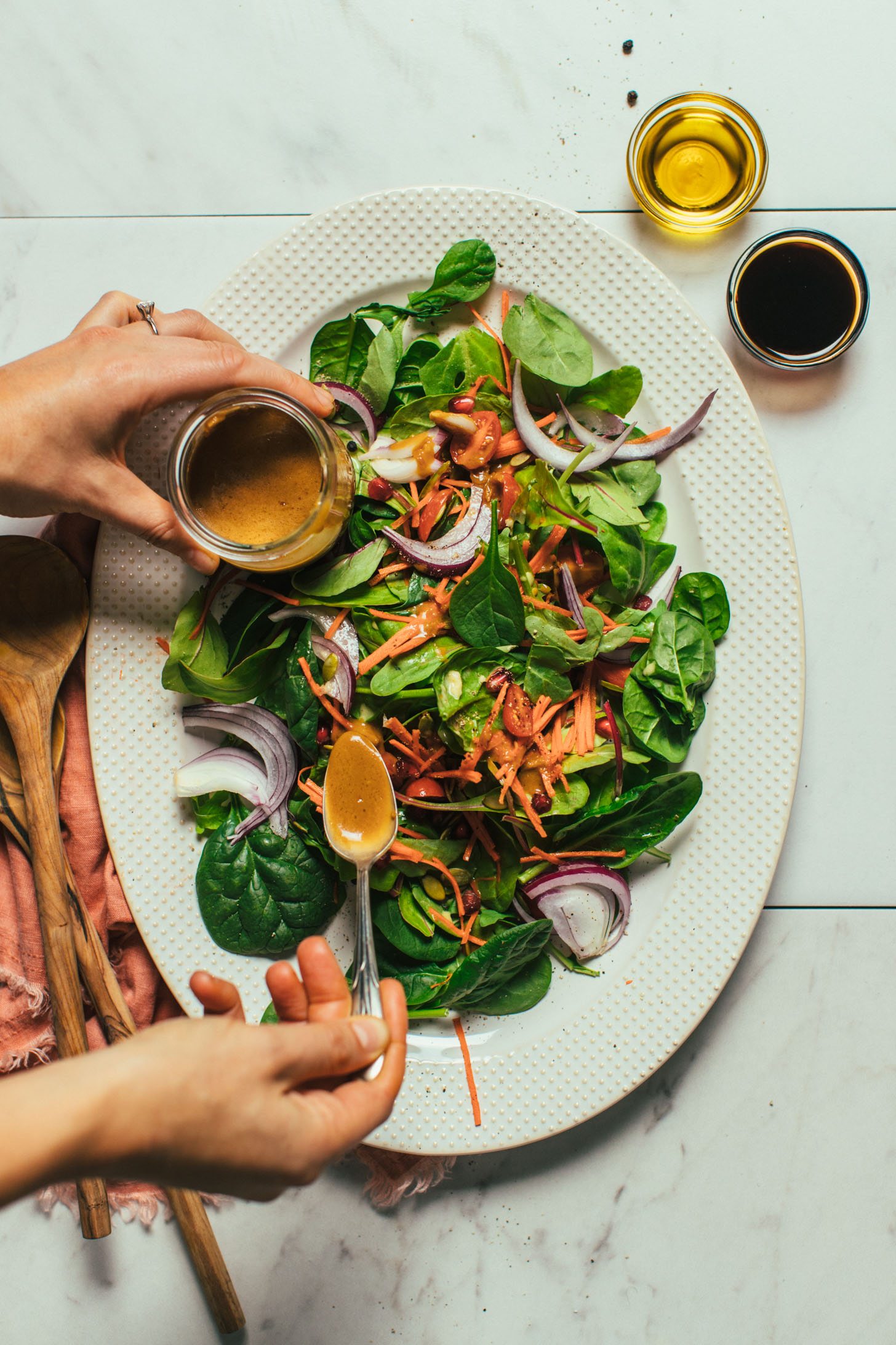 Holding a jar of dressing in one hand and using a spoon in the other hand to drizzle balsamic dressing on a salad