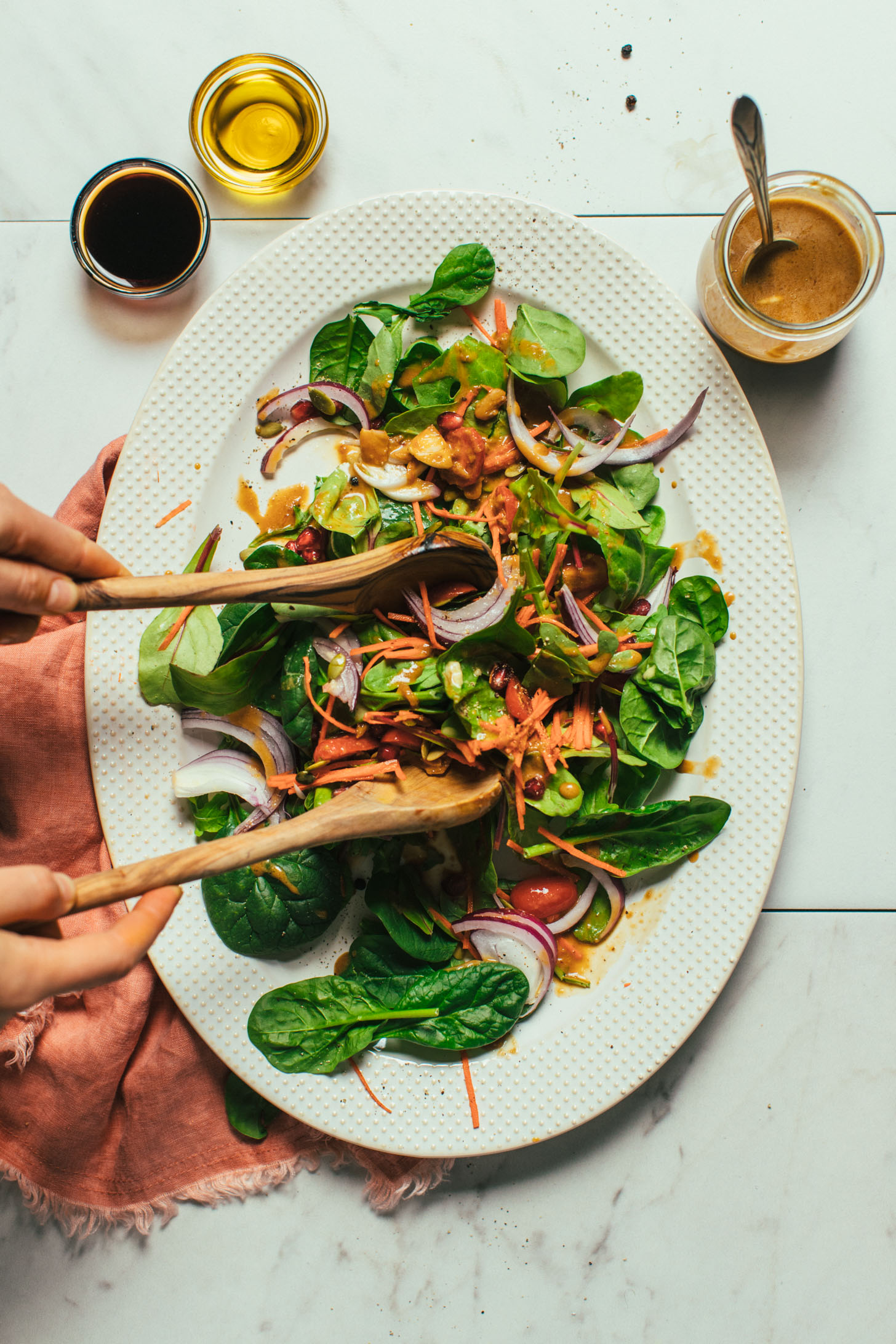 Using wooden salad spoons to toss a salad with homemade Balsamic Vinaigrette Dressing