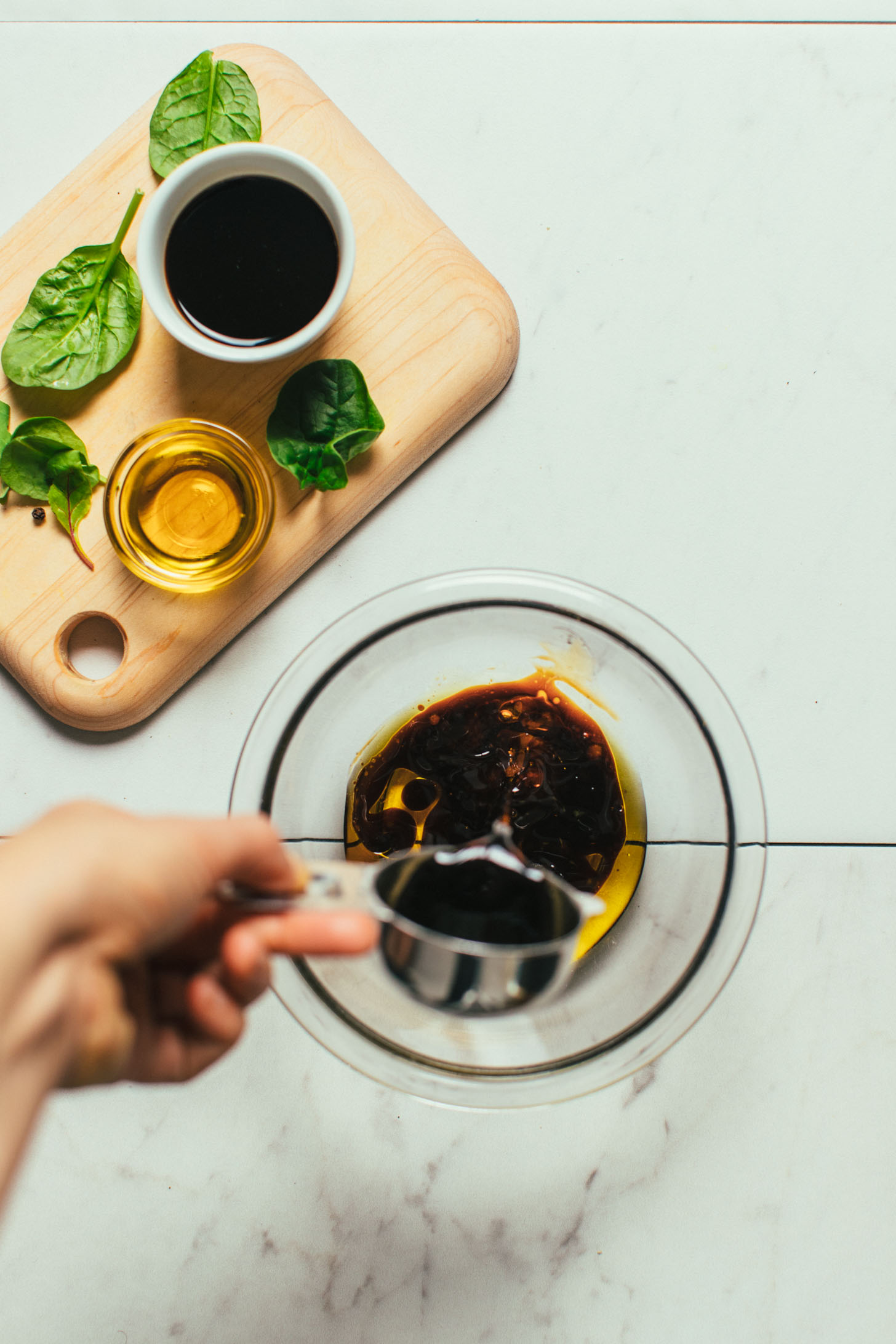 Pouring balsamic vinegar into a bowl for simple homemade dressing