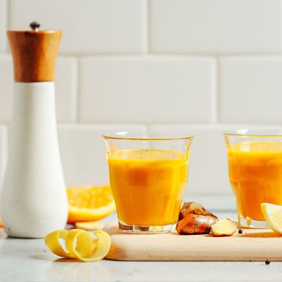 Glasses of our Lemon Ginger Turmeric Wellness Shots on a cutting board with ingredients to make them