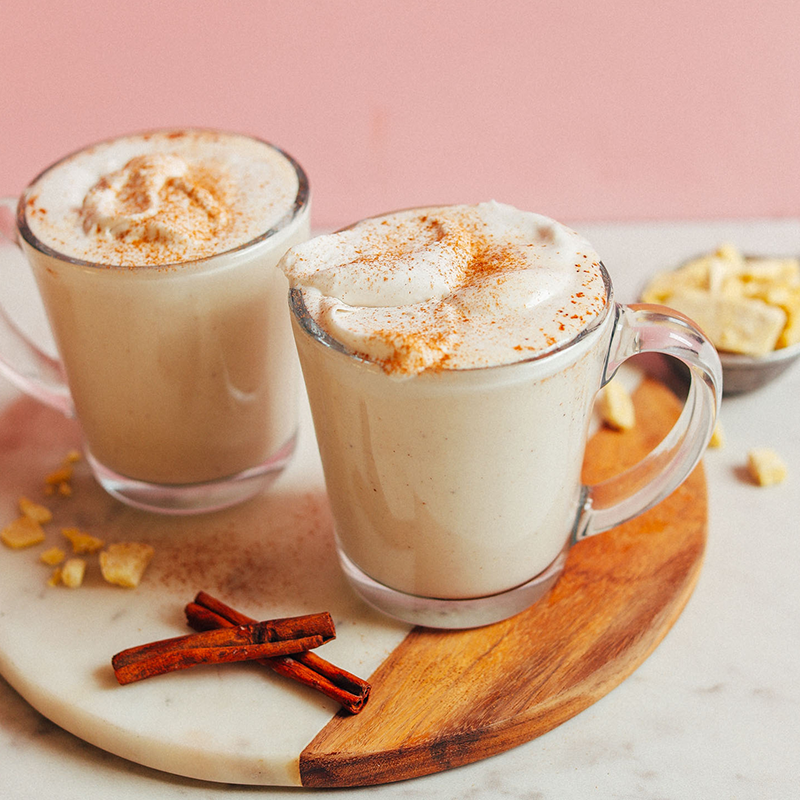 Two glass mugs filled with our Vegan White Hot Chocolate recipe alongside cinnamon sticks and cacao butter