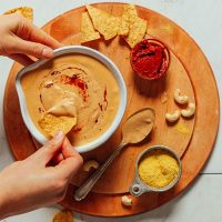 Dipping a chip into a bowl of Vegan Cashew Queso