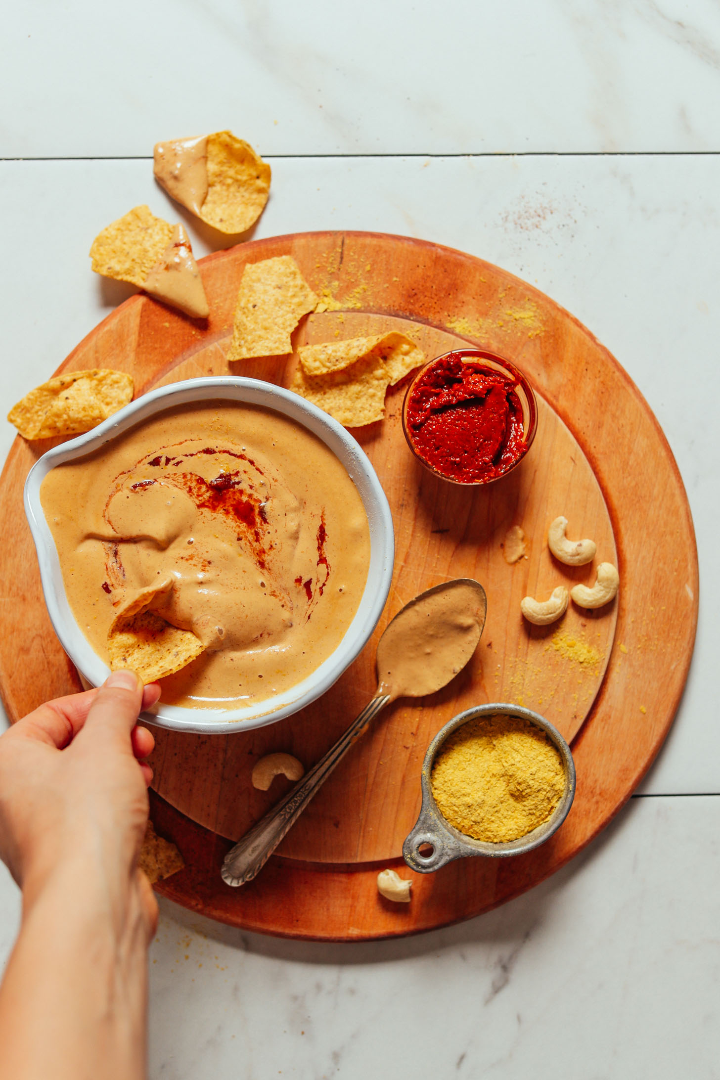 Overhead image of vegan cashew queso in a bowl with a hand dipping a dip