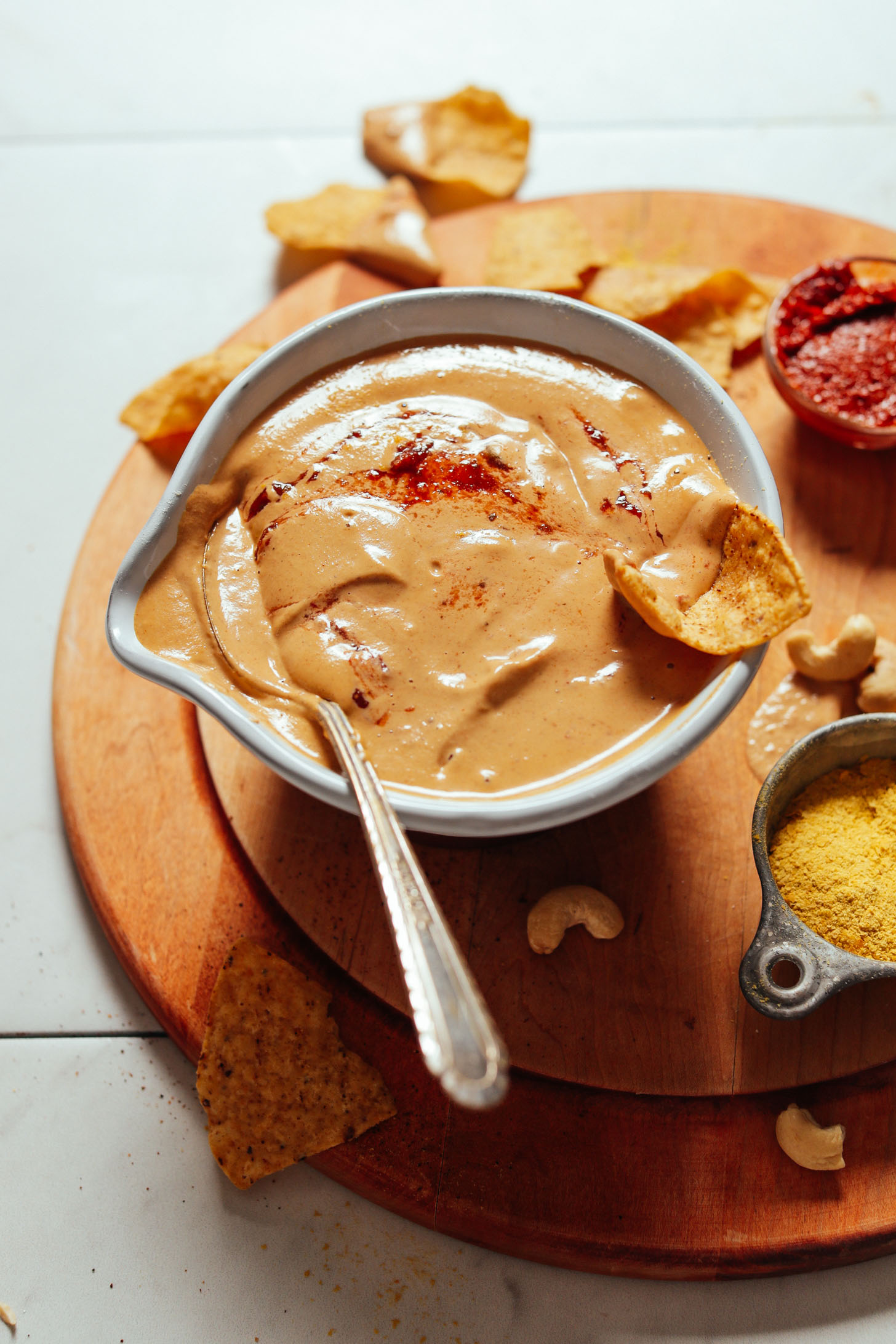 Image of vegan cashew queso in a bowl with a spoon on the left side and chip on the right side