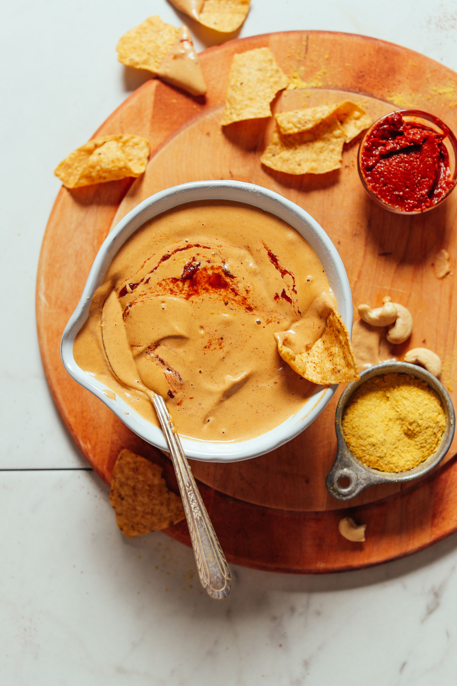 Overhead image of vegan cashew queso in a white bowl on a cutting board with harissa, chips, and nutritional yeast on the side