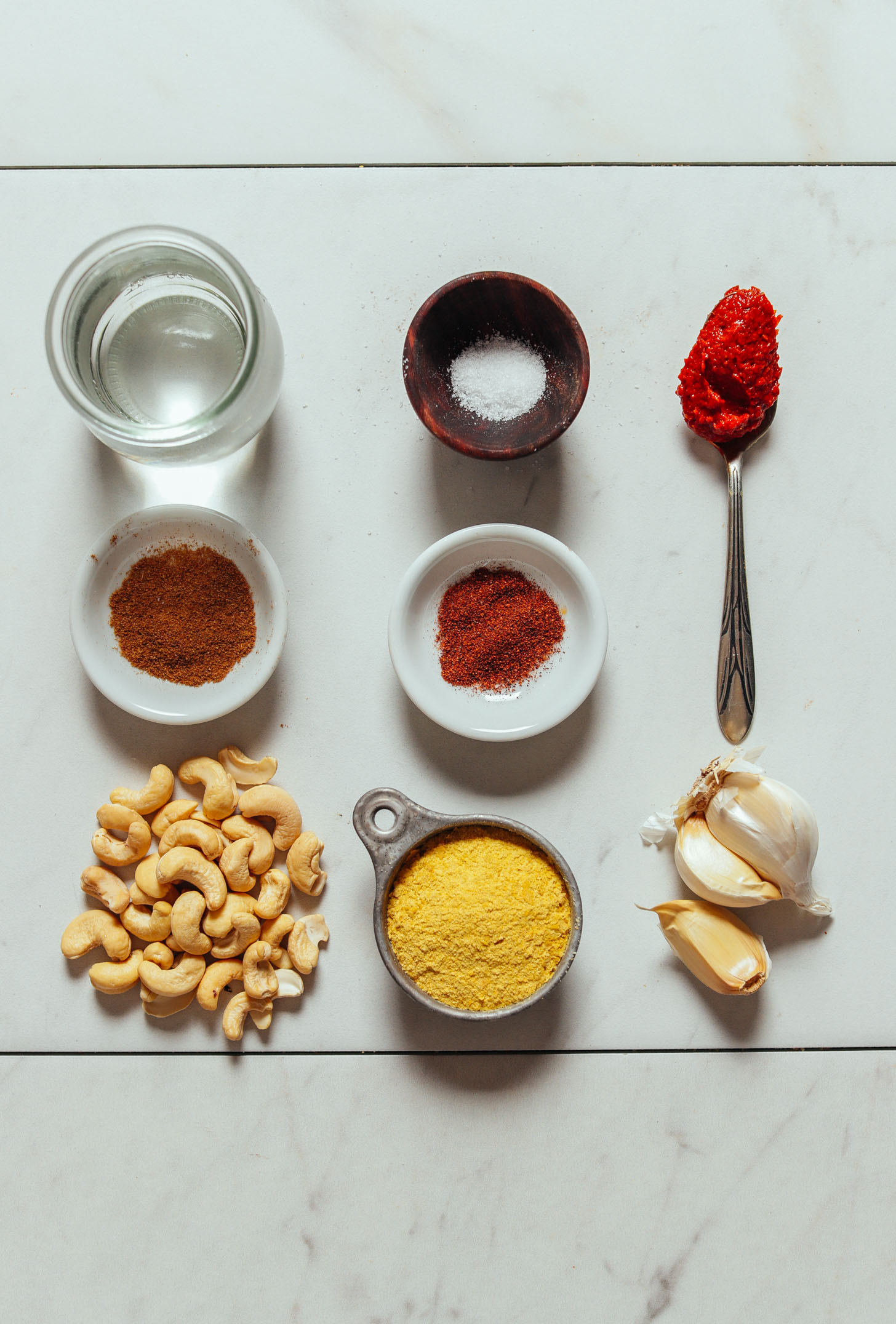 Overhead image of vegan cashew queso ingredients in a grid, including cashews, harissa, water, salt, and garlic
