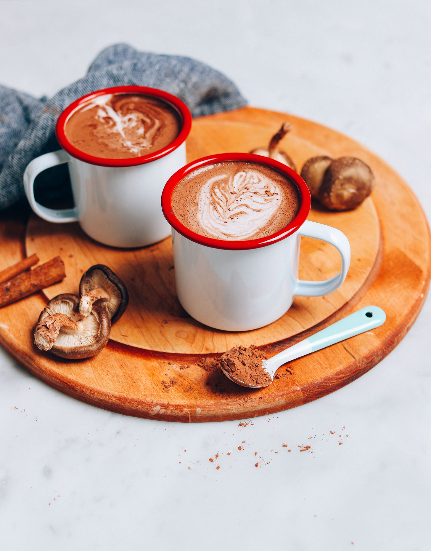 Straight on image of mushroom cacao hot latte on a cutting board with a blue towel, mushrooms in the background, and blue spoon of cacao powder in front