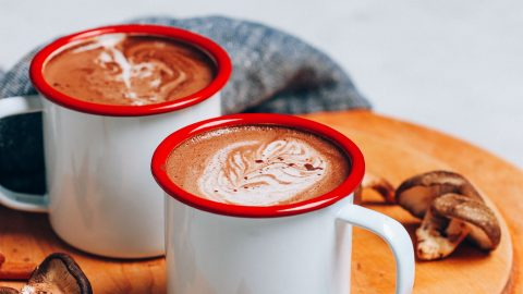 Hot cacao mushroom lattes on a cutting board with small spoon holding cacao powder in front and mushrooms near the back