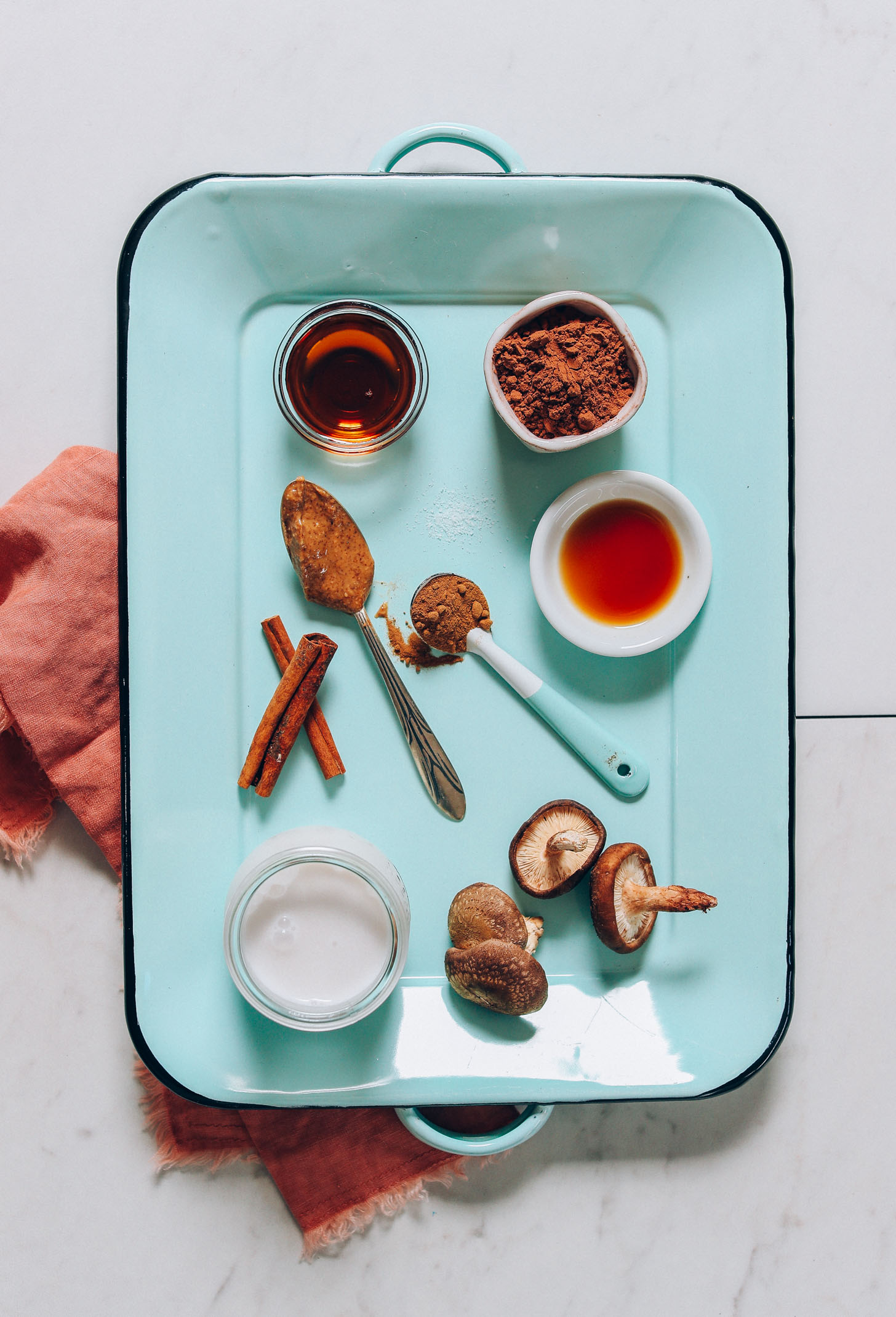 Overhead image of blue tray holding ingredients for mushroom hot cacao latte including mushroom powder, maple syrup, cinnamon, and coconut milk