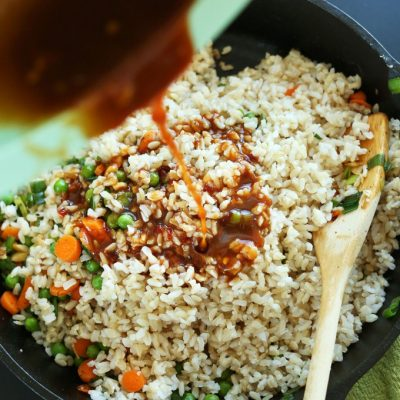 Pouring sauce into a pan of rice made with our How to Cook Brown Rice tutorial