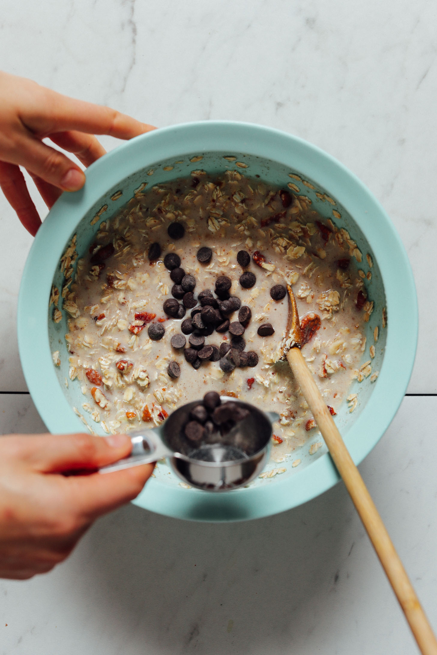 Overhead image of banana oatmeal in a blue bowl with chocolate chips being sprinkled on top