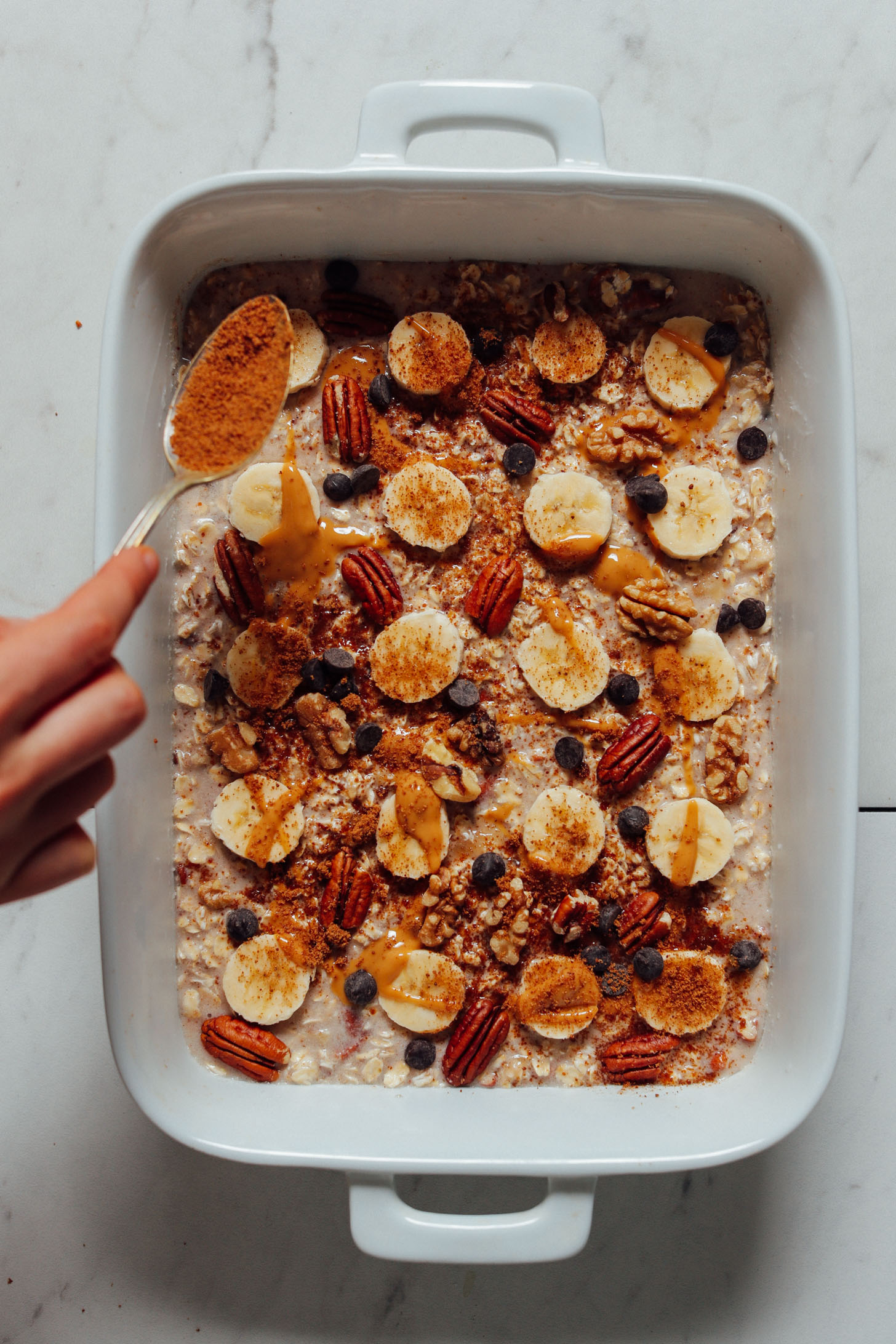 Overhead image of banana oatmeal in a baking dish lined with ripe banana being topped with a spoonful of coconut sugar