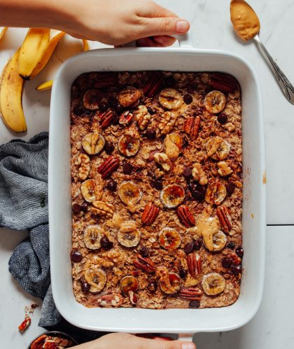 Overhead image of banana baked oatmeal with chocolate and nuts and hands holding the sides of the dish