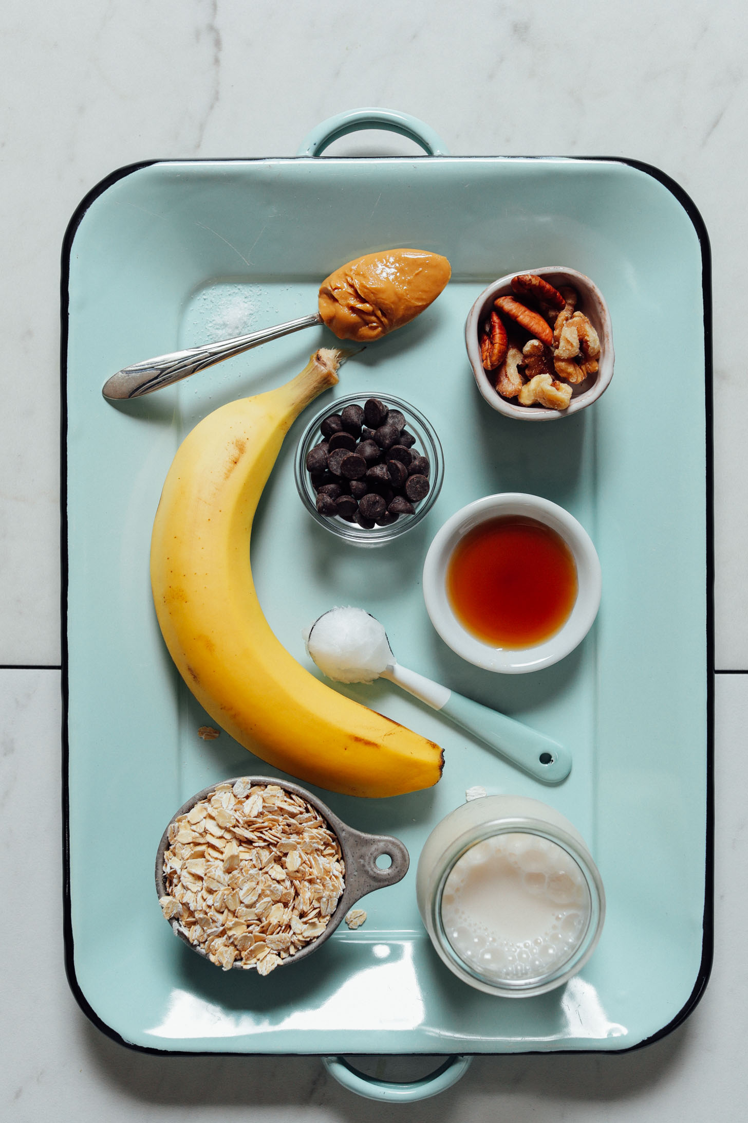 Overhead image of banana baked oatmeal ingredients on a blue tray, including oats, banana, and chocolate