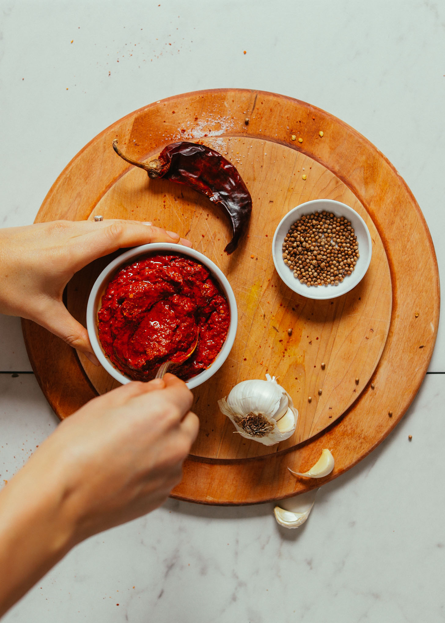 Overhead image of harissa paste in a white dish on a cutting board with a spoon stirring the sauce, and coriander, garlic, and peppers on the side