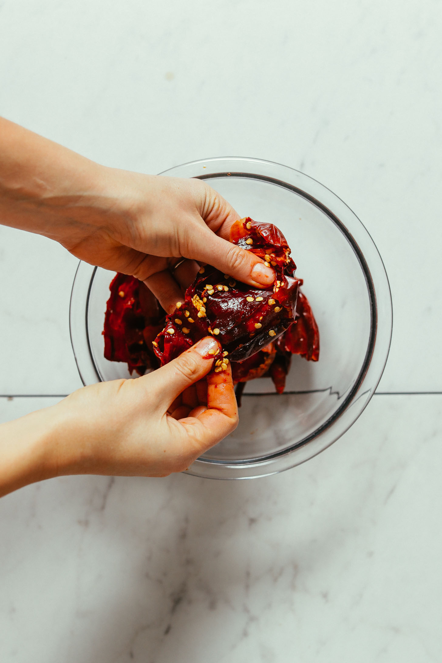Showing how to remove the seeds from soaked peppers for making our DIY Harissa Paste recipe