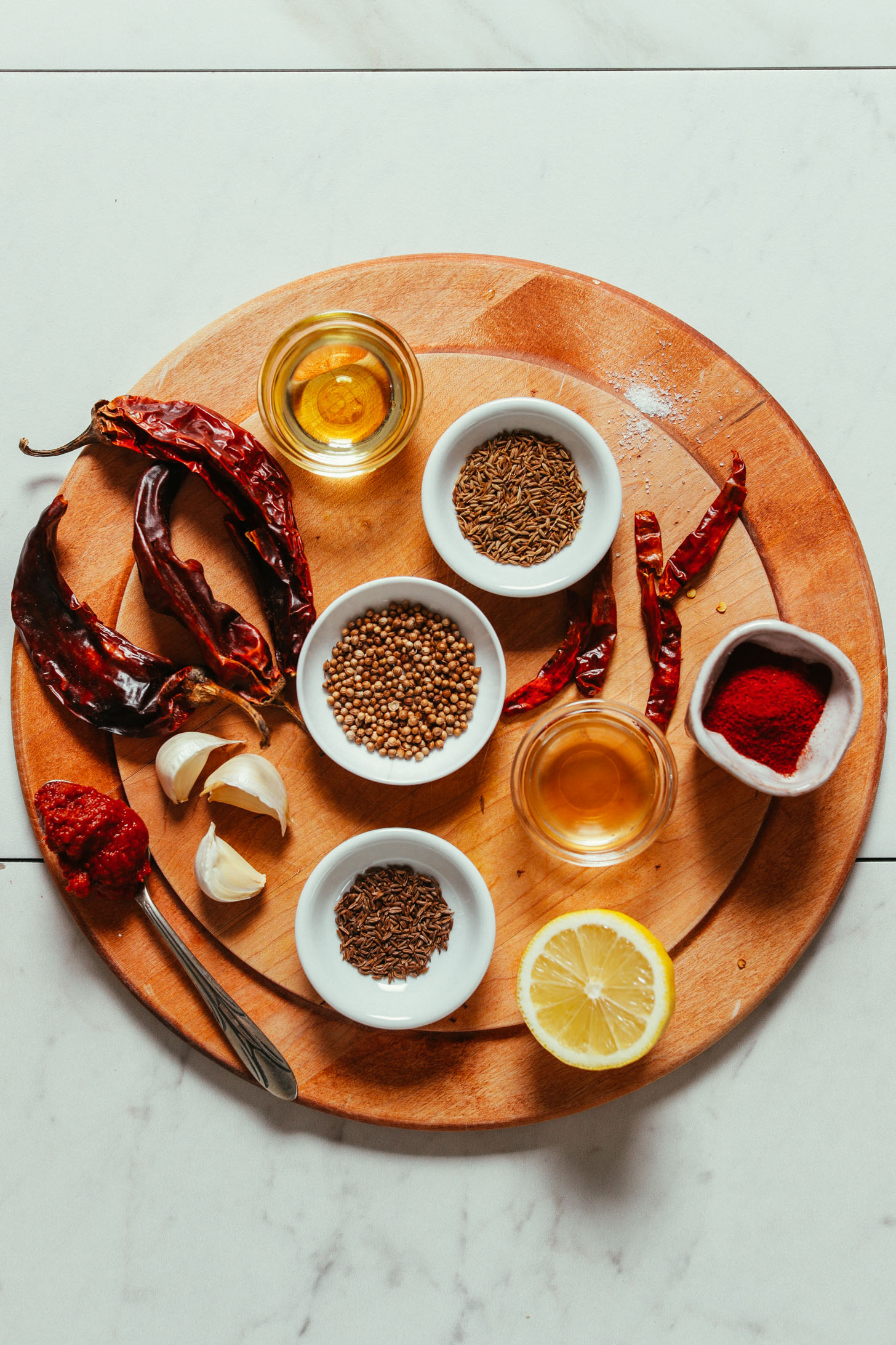 Overhead image of harissa ingredients on a cutting board, including dried chilies, smoked paprika, lemon, and garlic